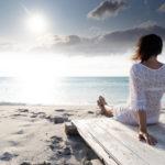 femme assise sur le sable qui regarde l'horizon
